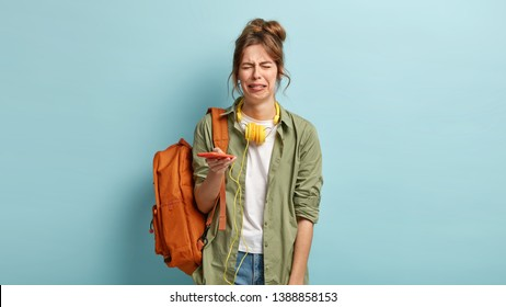 Miserable dejected hipster girl cries and sobs from despair, holds modern smart phone, has problem, cannot browse music app, dressed in casual shirt and jeans, carries rucksack on one shoulder