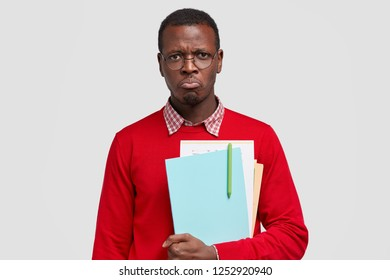 Miserable displeased offended black male college student, wants to cry from negative emotions, carries textbook with pen, feels fed up of studying, wears red sweater, isolated over white background