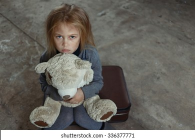 Miserable girl. Top view of little sad depressed girl holding her toy and begging for help while feeling unhappy