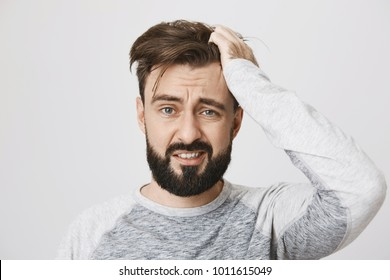 Miserable and gloomy guy with messy hair, frowning and looking unsatisfied while scratching head, standing over gray background. Something heavy fell on his head, man feels pain