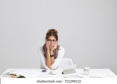Miserable gloomy overworked woman wears spectacles, has unhappy expression after sleepless night of working, sits at table with papers and electronic devices, dreams about holidays or good rest.