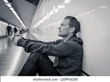 Miserable jobless young man crying Drug addict Homeless in depression stress sitting on ground street subway tunnel looking desperate leaning on wall alone in Mental disorder Emotional pain Sadness.