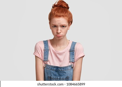Miserable stressed ginger female teenager wants to cry, feels lonely or abused by someone, has sullen expression, poses against white concrete studio wall. Unhappy red haired student fails exam