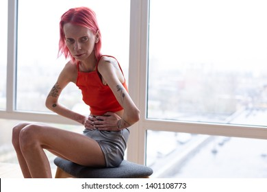Miserable woman. Unhealthy miserable woman with anorexia sitting near the window feeling awful