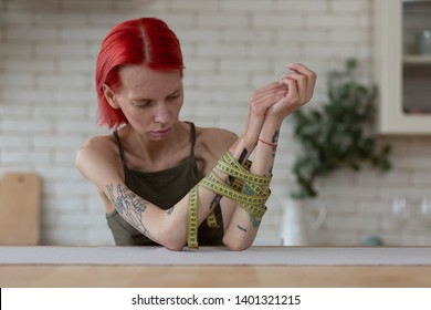 Miserable woman. Unhealthy skinny woman feeling miserable suffering from bulimia having tape measure on hands