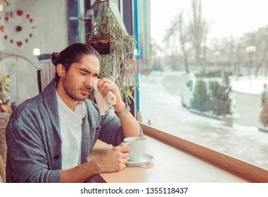 Misery, infelicity. Brunette Multicultural man guy about to cry wiping tears sneezing in a tissue drinking tea, coffee, hot beverage. Negative human emotion, face expression, reaction, body language