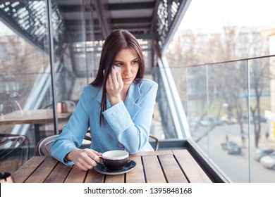 Misery, infelicity. Brunette woman girl about to cry wiping tears sneezing in a tissue drinking tea, coffee, hot beverage. Closeup portrait of a beautiful hispanic girl wearing formal blue suit