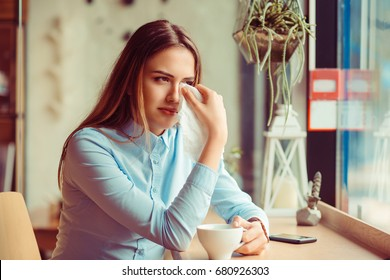 Misery, infelicity. Brunette woman girl about to cry wiping tears sneezing in a tissue drinking tea, coffee, hot beverage. Negative human emotion, face expression, reaction, body language