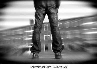 Misfit young man with scattered legs standing in front of a building with zoom and stripes in black and white tv effect