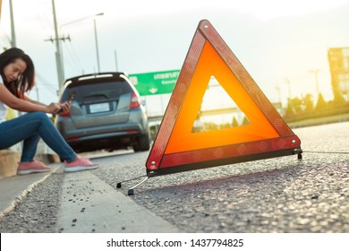 Misfortune asian woman texting for help, Red warning triangle. Focus on red triangle!