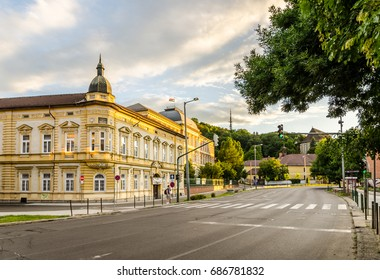 MISKOLC, HUNGARY - 27 JULY, 2017: The end of a sunny day in the city of Miskolc in Hungary. Empty street and green traffic lights surrounded by historic buildings