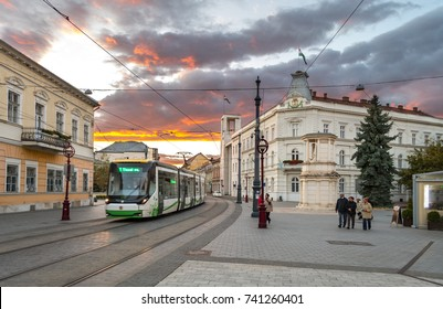 MISKOLC, HUNGARY - 8 OCTOBER, 2017: A Skoda tram crossing the historic main square of Miskolc, Hungary with the building of the municipality in the background