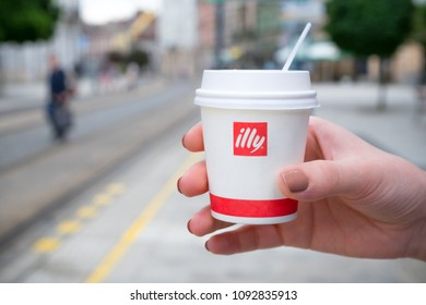 MISKOLC, HUNGARY - MAY 17, 2018: Female hand holding an Illy paper coffee cup in a tram stop