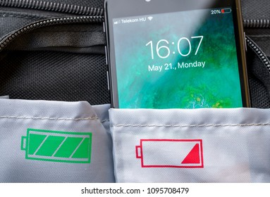 MISKOLC, HUNGARY - MAY 21, 2018: iPhone 8 with low battery by the end of a working day in a pocket with a red low battery sign on it. Concept of cell phone batteries dying by the end of a work day.