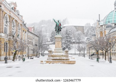 Miskolc in winter: Elisabeth square with the statue of Lajos Kossuth and the Avasi Church in the background covered in snow
