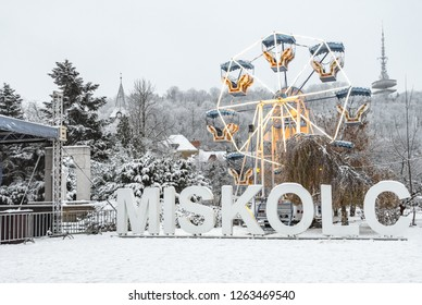 Miskolc in winter: Miskolc letters in the city center at the Christmas fair with a ferris-wheel, Avas Church in the background