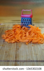 Mismatch: a large carrot next to a small grater. Cutting board on the kitchen table. Unusual mystery and optical illusion