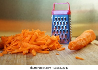 Mismatch: a small grater and a large carrot are on the cutting board. Unusual mystery and optical illusion.