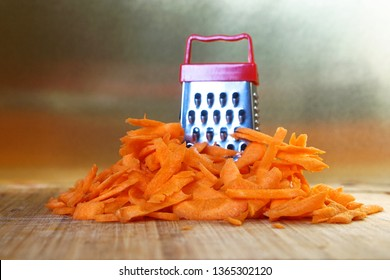 Mismatch: a small grater next to a large carrot. Cutting board on the kitchen table. Unusual mystery and optical illusion. Closeup