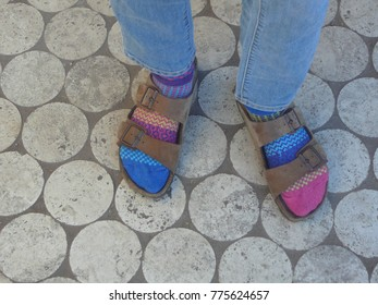 Mismatched colorful socks being worn with a pair of sandals