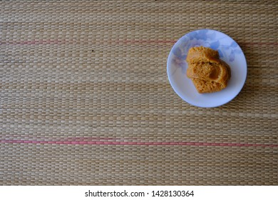 Miso on the dish on the reed or papyrus mat, is the ingredient for make a braised large intestine with miso the miso paste made from fermented soybeans and barley or malt, used in Japanese cooking.