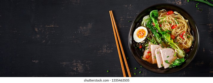Miso Ramen Asian noodles with egg, pork and pak choi cabbage in bowl on dark background. Japanese cuisine. Top view. Banner