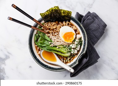 Miso Ramen Asian noodles with egg, enoki and pak choi cabbage in bowl on white marble background