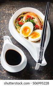 Miso Ramen Asian noodles with egg, shrimp, green onions, chili peppers in a white bowl. Dark background