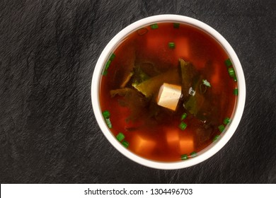 Miso shiru soup with tofu, scallions, and wakame seaweed, shot from the top on a black background with copy space