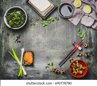 Miso soup cooking ingredients on rustic vintage background with chopsticks, top view, frame. Asian food or Japanese cuisine concept