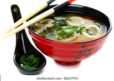 Miso soup with seafood and green onions on a white background.