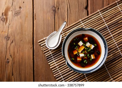 Miso Soup with tofu in bowl on bamboo background