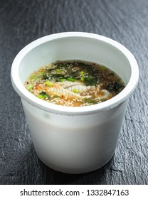 Miso unagi soup over slate plate background in take-out container