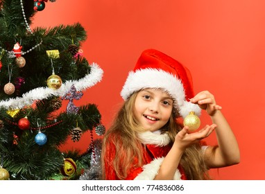 Miss Santa holds golden ball for Christmas tree. Kid with happy face decorates tree with toy on red background, copy space. New year gift concept. Girl in xmas hat with decor