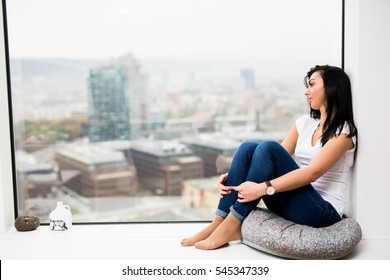 I miss you. Woman sitting on window looking out