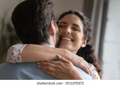 I missed you so much. Excited millennial wife embracing neck of beloved husband meeting at home on return from business trip. Happy young couple cuddling celebrating reunion reconciling after quarrel