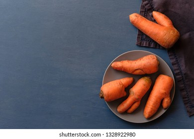 Misshapen ugly fresh carrots with imperfections and splits on a plate viewed from overhead on grey with copy space