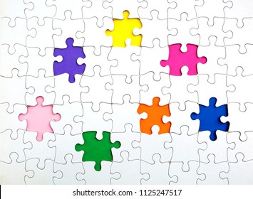 Missing few white  puzzle pieces on the rainbow colours background
