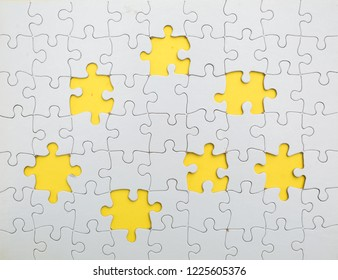 Missing few white  puzzle pieces on yellow background