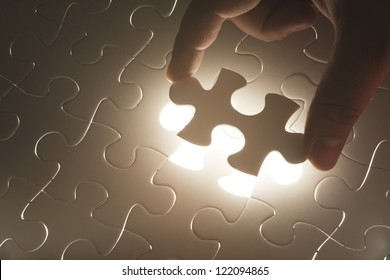 Missing jigsaw puzzle piece with light glow, business concept for completing the final puzzle piece