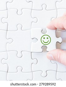 Missing jigsaw puzzle piece with smiling emoticon face. Business concept image for completing the puzzle.