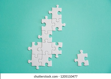Missing jigsaw puzzle pieces. Business concept. Fragment of a folded white jigsaw puzzle and a pile of uncombed puzzle elements against the background of a colored surface.