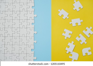 Missing jigsaw puzzle pieces. Business concept. Fragment of a folded white jigsaw puzzle and a pile of uncombed puzzle elements against the background of a yellow surface.