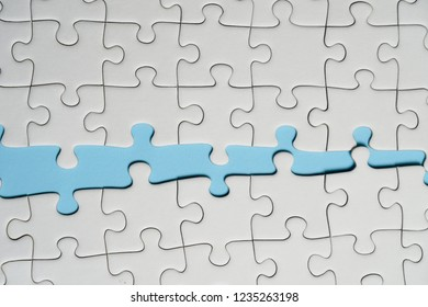 Missing jigsaw puzzle pieces. Business concept. Fragment of a folded white jigsaw puzzle and a pile of uncombed puzzle elements against the background of a blue surface.