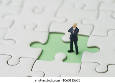 Missing key person for business success strategy concept, miniature people businessman standing  at the missing white jigsaw puzzle piece on pastel green background.