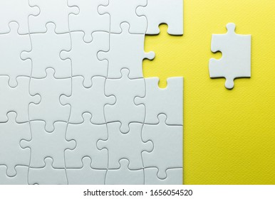 A missing piece to complete a puzzle, white pieces on a yellow background with texture.teamwork