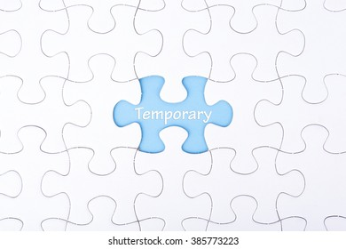 Missing a piece of puzzle in the center, blue space with word TEMPORARY, business and financial concept.