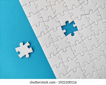 Missing piece of the puzzle, white puzzle pieces on blue background