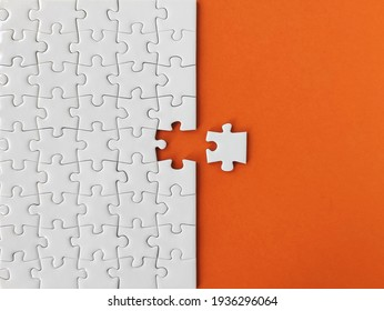 Missing piece of the puzzle, white puzzle pieces on orange background