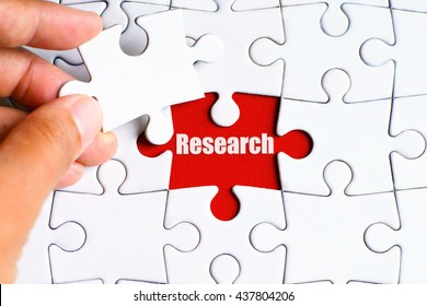 "A missing puzzle with a hand hold a piece of ""Research"" text puzzle want to complete it - business and finance conceptt"